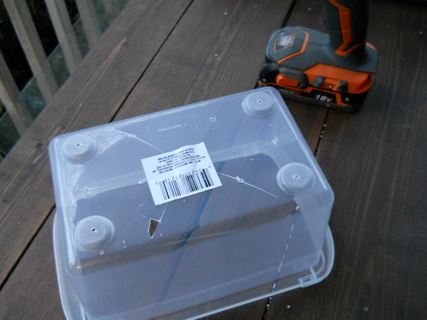 Drilling drainage holes in a plastic storage container from Dollar Tree